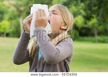 Close-up of a young girl sneezing into tissue paper at the park
