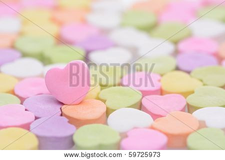 Closeup of a pink candy heart for Valentines Day standing out in a field of out of focus similar candies. Heart is set to one side leaving room for your copy. The candies are blank.
