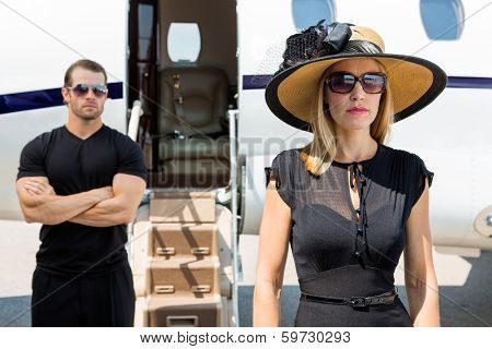 Beautiful woman wearing sunhat with bodyguard and private jet in background