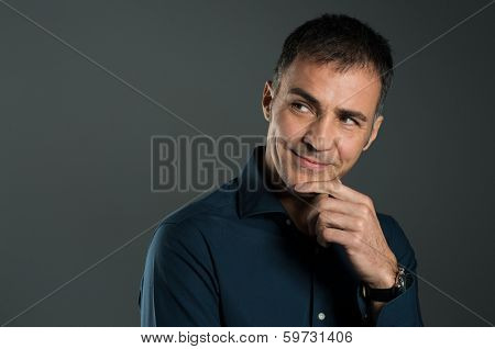 Portrait Of Mature Man Thinking A Strategy With Hand On Chin On Grey Background