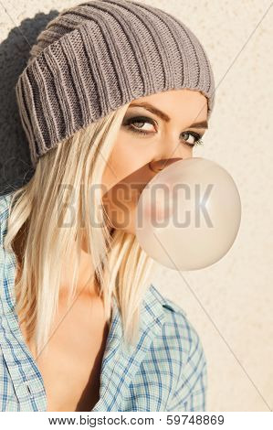 Beautiful Blonde Girl In Beanie Hat With Smokey Eye Make Up Who Enjoys Blows Big Bubble From Bubble