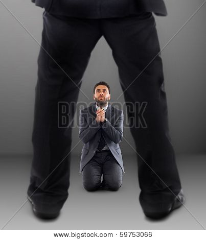 Business Man On His Knees Praying Not To Be Dismissed