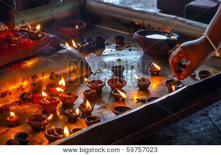 the hand lighting candles in the Indian temple