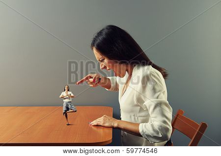 angry young woman screaming and pointing at small calm woman