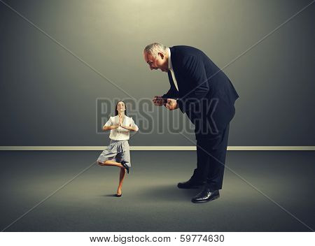 angry big boss screaming at small meditation businesswoman