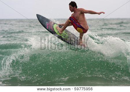 Male Surfer Rides Top Of Wave Off Florida Coastline