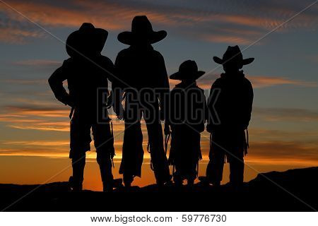 Beautiful Silhouette Of Four Young Cowboys With A Sunset Background