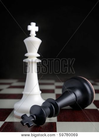 Black King lying on chessboard by the winning white King