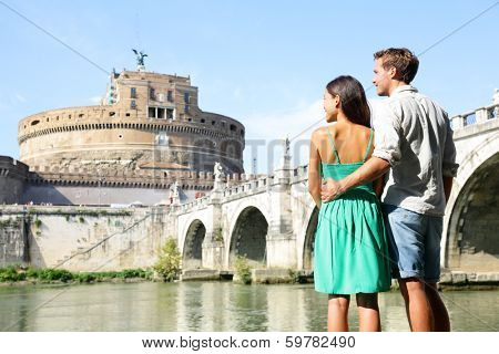 Rome travel tourists by Castel Sant'Angelo. Happy romantic couple looking at the roman castle enjoying their romantic summer holidays travel in Italy, Europe. Man and woman embracing.