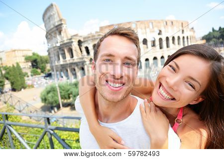 Happy travel couple in piggyback by Coliseum, Rome, Italy. Smiling young romantic couple in love traveling in Europe having fun together in front of Colosseum. Caucasian Man and Asian woman portrait