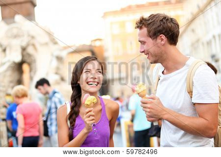 Ice cream - couple eating gelato in Rome on Piazza Navona. Couple eating ice cream on vacation travel in Italy, Europe. Smiling happy young couple in love having fun eating italian food outdoors.