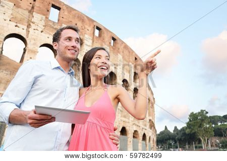 Happy travel couple with tablet by Coliseum, Rome, Italy. Smiling young romantic couple traveling in Europe using tablet pc computer with guidebook or map in front of Colosseum. Man and woman together