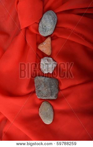 Five stones on red satin