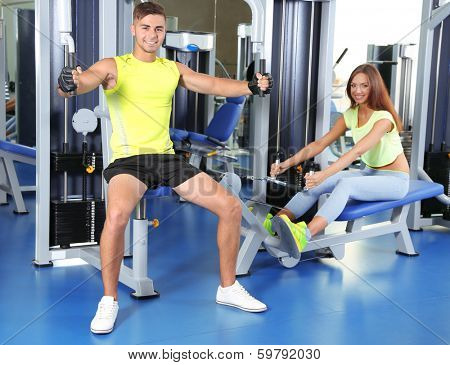 Guy and girl engaged in simulator at gym
