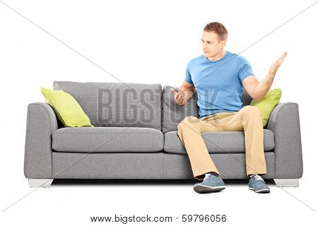 Angry man sitting on couch and swinging his hand violently isolated on white background