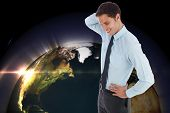 Thinking businessman scratching head against glowing earth, elements of this image furnished by NASA