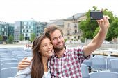 Tourist couple on travel in Berlin, Germany on boat tour cruise smiling happy taking selfie self-por