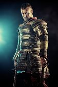 stock photo of sword  - Portrait of a courageous ancient warrior in armour with sword - JPG