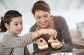 stock photo of cream puff  - Mother and daughter preparing cream puffs - JPG