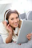 Smiling woman listening to music with tablet and headphones