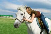 stock photo of white horse  - The young beautiful girl embraces a white horse - JPG