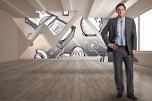 Smiling businessman with hand on hip against profit graphic on abstract screen in room