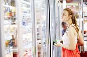 foto of refrigerator  - Young woman buying dairy or refrigerated groceries at the supermarket in the refrigerated section opening glass door of the fridge