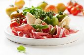 foto of antipasto  - Italian antipasto with ham green and red tomato olive basil rosemary and red wine selective focus