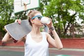 Beautiful  Lady In White T-shirt With Skateboard And To-go Cup At Sport Court