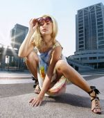 stock photo of snob  - Beautiful blonde woman takes sunglasses on urban background - JPG