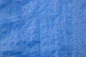 stock photo of tarp  - Closeup of rain drops on blue tarp material - JPG