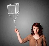 Pretty young woman holding a drawn cube balloon