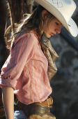stock photo of cowgirls  - Cowgirl with white cowboy hat in a stone barn