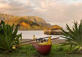 foto of na  - Red and yellow hawaiian canoe with outrigger on the beach at Hanalei pier at dawn as the sun lights the sky over Na Pali mountains - JPG