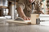 stock photo of joinery  - young worker at work in joinery while using a circular saw - JPG