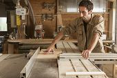 stock photo of workbench  - young worker at work in joinery while using a circular saw - JPG