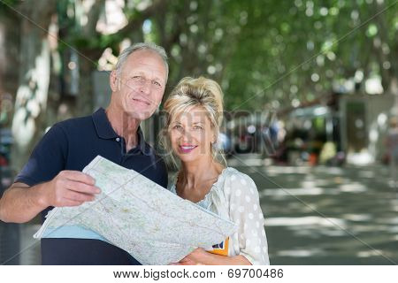 Mature Couple On Vacation Looking At A Map