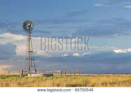 windmill with a pump  and cattle water tank in shortgrass prairie, Pawnee National Grassland in Colorado near Grover