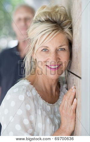 Smiling Woman Resting Her Cheek On A Wall