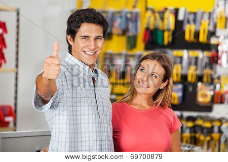 Portrait of successful man gesturing thumbsup with woman in hardware store