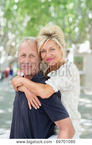 Man Giving A Smiling Woman A Piggy Back Ride