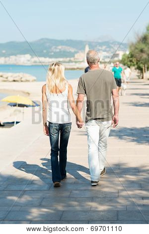 Couple Walking On A Seafront Promenade