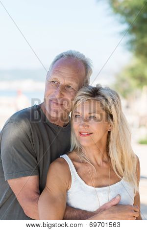 Loving Couple Watching Something At The Beach