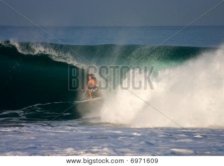 A surfer inside the barrel of a wave