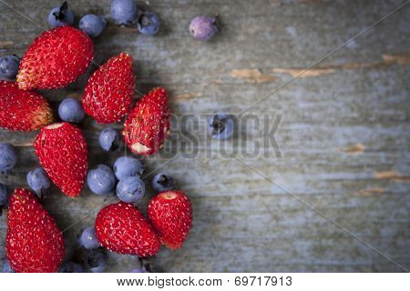 Fresh small wild strawberries and blueberries on old blue wooden background with copy space