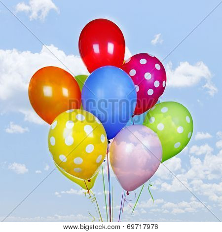Colorful helium balloons on blue sky with clouds