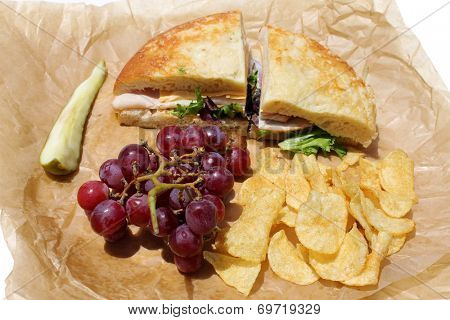 A picnic lunch with a Turkey and Cheese Sandwich on Cheese Bread, Chips, Red Grapes and a Dill Pickle Slice wrapped in deli paper, isolated on white. Deli Sandwiches are a favorite for picnics