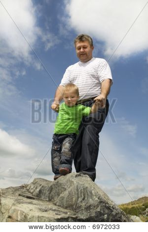 Father And Son Standing At The Edge Of Rock