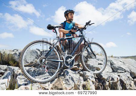 Fit cyclist taking a break on rocky peak on a sunny day