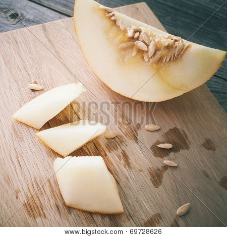 Slices Of Honeydew Melon On Gray Wooden Table
